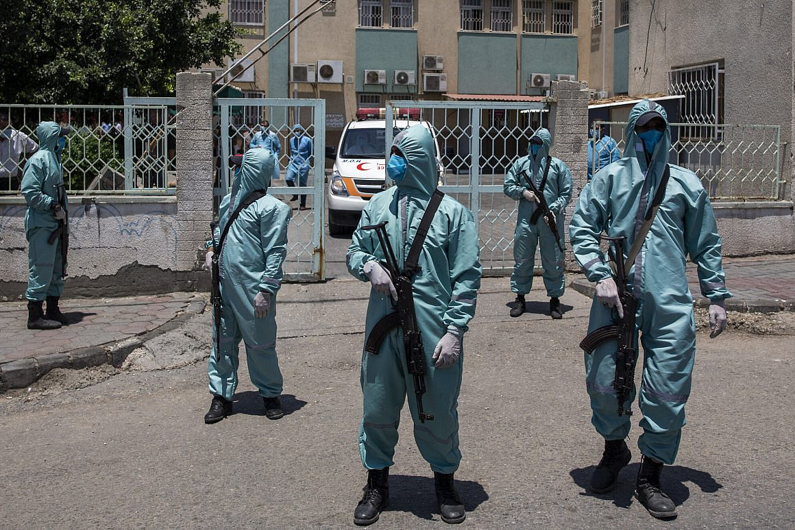 Palestinian Hamas police officers wear protective suits as they take part in a simulation of possible coronavirus infections in Gaza City, Saturday, July 18, 2020. (AP Photo/Khalil Hamra)
