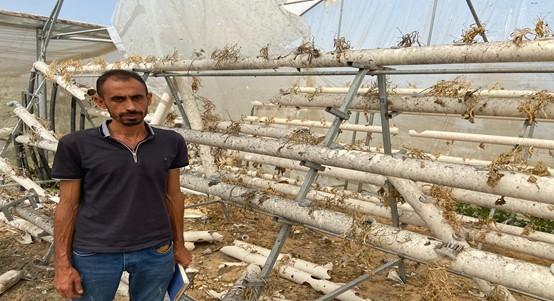 Abu Halima next to the damaged greenhouse. Photo by Mohammed Azaiza