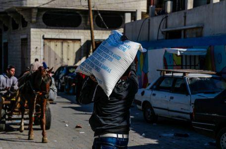 אדם נושא שק מזון, עזה. צילום: גישה