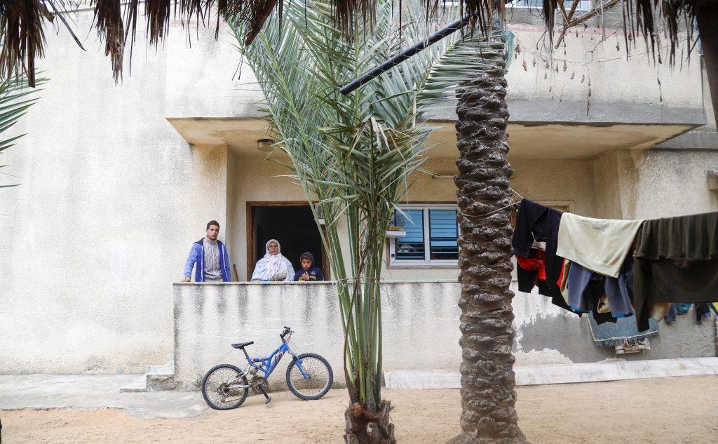 משפחת אלשיך בכניסה לביתם. צילום: אסמאא ח'אלידי