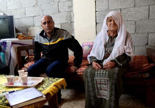 He prefers to live in a half-destroyed house, where the rains come in from every direction. Ayman Abu Odeh and his mother. Photo: Gisha