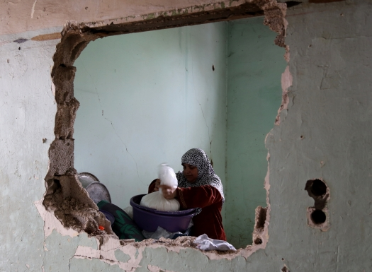 The building was declared unfit to live in. Ayman Abu Odeh's wife. Photo: Gisha