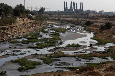 Sewage in Wadi Gaza, with Gaza's sole power plant in the background